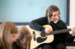 Girl practicing guitar in classroomの写真素材 [FYI02115537]