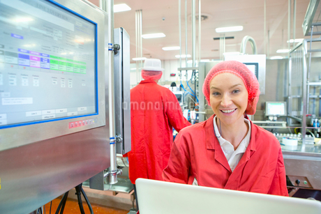 Portrait smiling worker at control panel on production line food processing plantの写真素材 [FYI02115548]