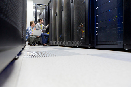 Technicians with laptop checking server in data centreの写真素材 [FYI02115556]