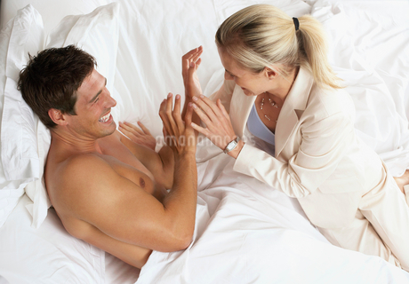 Couple laughing and joking in bed, side view, elevated viewの写真素材 [FYI02115564]