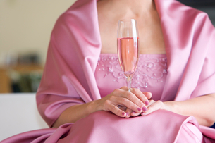 Senior woman, in pink dress, holding champagne flute at wedding, front view, close-up, mid-sectionの写真素材 [FYI02115606]