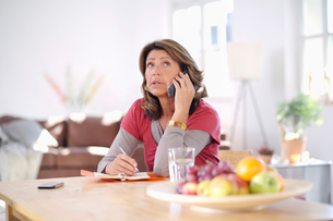 Mature woman at home on the phoneの写真素材 [FYI02115618]