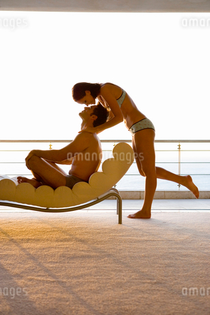 Young woman standing by man sitting on chaise lounge by balcony, side viewの写真素材 [FYI02115633]