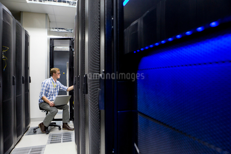 Technician with laptop checking server in data centreの写真素材 [FYI02115634]