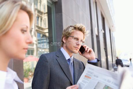 Businessman talking on cell phone standing next to businesswoman, Stuttgart, Baden-Wurttemberg, Germの写真素材 [FYI02115655]
