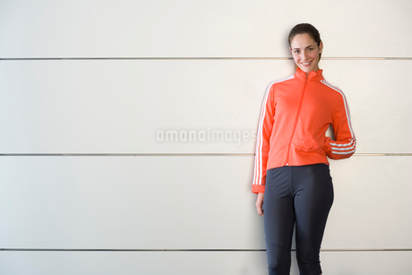 Woman in fitness clothes with hand in pocket, smiling, portraitの写真素材 [FYI02115659]