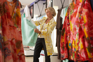 Mature blonde woman shopping in clothes shop, choosing between two different coloured tops, side vieの写真素材 [FYI02115662]