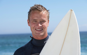 Young man in wetsuit standing on beach with surfboard, smiling, front view, close-up, portraitの写真素材 [FYI02115692]