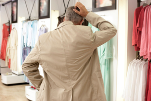 Mature man shopping in clothes shop, scratching head, hand on hip, rear viewの写真素材 [FYI02115696]