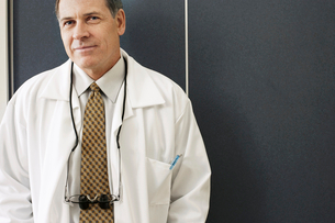 Male dentist standing in dental surgery, smiling, front view, portraitの写真素材 [FYI02115704]