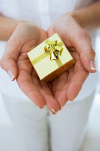Mature woman holding small gold gift box in cupped hands, close-up, front view, mid-sectionの写真素材 [FYI02115708]