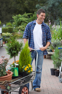 Man shopping in garden centre, pushing trolley full with pot plants, smilingの写真素材 [FYI02115709]