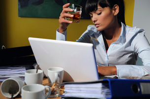 Portrait of woman drinking alcohol at workの写真素材 [FYI02115734]