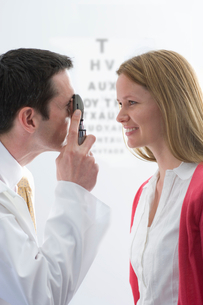 Doctor examining female patientユs eyes with ophthalmoscopeの写真素材 [FYI02115764]