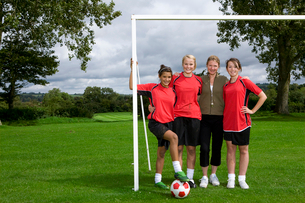 Portrait of teenage girls and soccer coach standing at goalの写真素材 [FYI02115768]