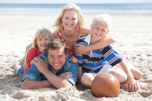 Portrait of smiling family laying on sunny beachの写真素材 [FYI02115802]