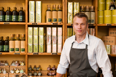 Male grocery shop owner in apron standing beside olive oil shelf display, smiling, portraitの写真素材 [FYI02115829]