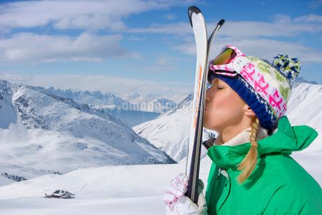 Woman kissing skis on snowy mountainの写真素材 [FYI02115866]