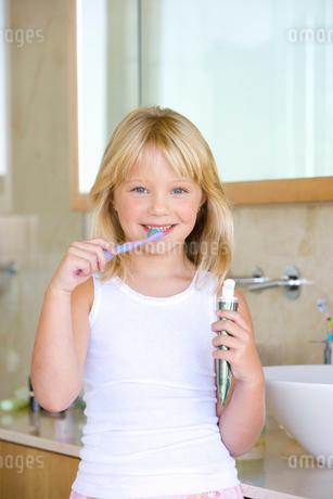 Girl (6-8) brushing teeth in bathroom, smiling, portraitの写真素材 [FYI02115886]
