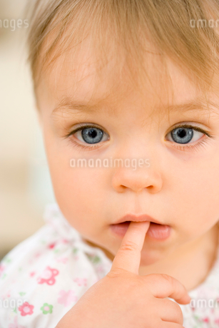 Baby girl (9-12 months) with finger in mouth, close-upの写真素材 [FYI02115905]