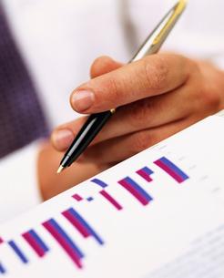 Close up of businessman holding pen near bar graphの写真素材 [FYI02115908]