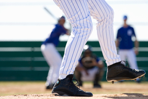 Young men playing baseball, focus on pitcher in foreground, low-section, rear viewの写真素材 [FYI02115914]