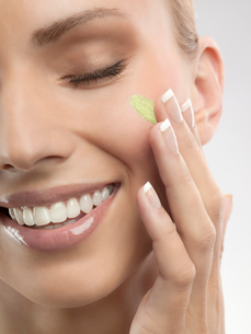 A woman putting green cream on her faceの写真素材 [FYI02115923]