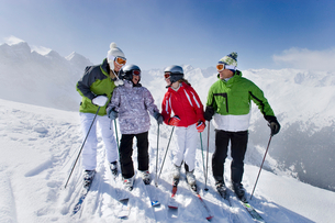 Family of skiers smiling together on mountain topの写真素材 [FYI02115932]