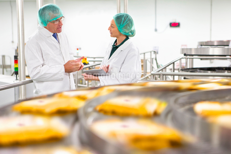 Quality control workers talking behind production line in cheese processing plantの写真素材 [FYI02115979]