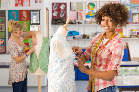 Smiling student sewing clothing in home economics classroomの写真素材 [FYI02115997]