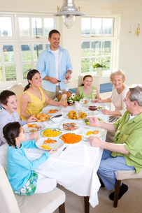 Multi-generation family eating dinner at dining room tableの写真素材 [FYI02115999]