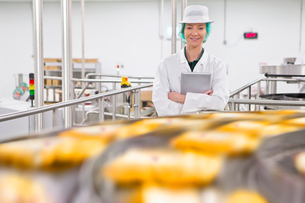 Portrait confident quality control worker at production line in cheese processing plantの写真素材 [FYI02116010]