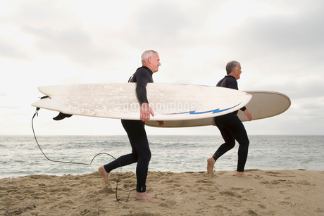 Male surfers in wetsuits on beach, side viewの写真素材 [FYI02116019]