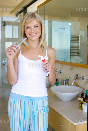 Young woman holding toothbrush in bathroom, smiling, portraitの写真素材 [FYI02116025]