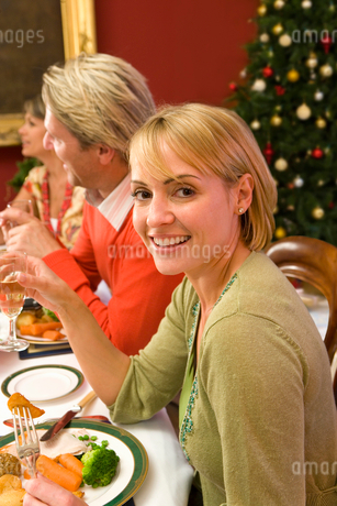 Family having Christmas dinner, portrait of young womanの写真素材 [FYI02116047]