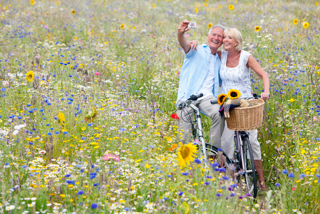 Senior couple on bicycles in field of wildflowers taking self-portraitの写真素材 [FYI02116068]