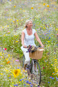 Smiling woman riding bicycle on path through field of wildflowersの写真素材 [FYI02116076]