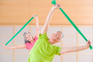 Portrait of senior man and woman exercising with resistance bands in gymの写真素材 [FYI02116078]