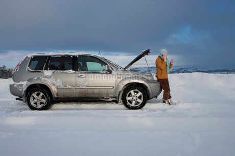 Woman standing in snow checking underneath car's hood and talking on cell phoneの写真素材 [FYI02116079]