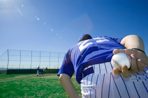 Baseball pitcher, in blue uniform, preparing to throw ball during competitive game, holding ball behの写真素材 [FYI02116093]