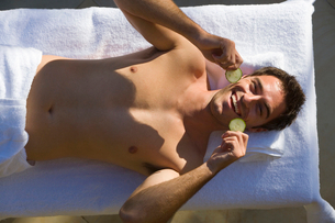 Bare chested man having beauty treatment, holding cucumber slices, smiling, portrait, overhead viewの写真素材 [FYI02116099]