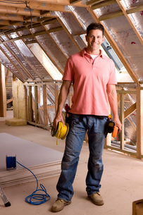 Smiling electrician standing in attic under constructionの写真素材 [FYI02116100]