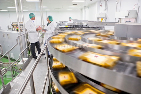 Quality control workers talking behind production line in cheese processing plantの写真素材 [FYI02116115]