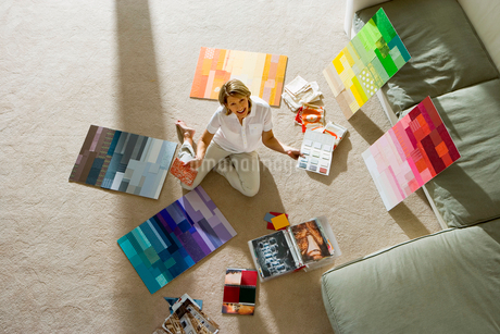 Mature woman sitting on floor at home, looking at colour charts, smiling, portrait, overhead viewの写真素材 [FYI02116118]
