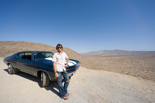 Young man with water bottle in sunglasses by car in desertの写真素材 [FYI02116149]