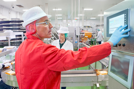 Worker at control panel at production line in cheese processing plantの写真素材 [FYI02116179]