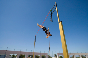 Male pole vault athlete going over bar, low angle viewの写真素材 [FYI02116197]