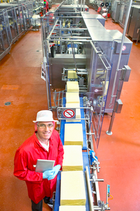 High angle view portrait of smiling quality control worker with digital tablet at production line inの写真素材 [FYI02116198]