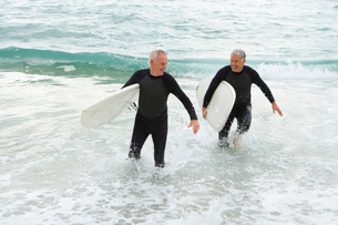 Male surfers in wetsuits in shallow waterの写真素材 [FYI02116213]