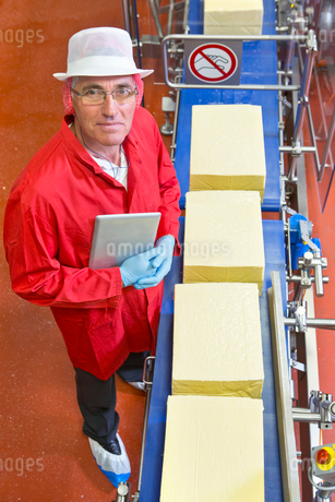 High angle view portrait confident quality control worker with digital tablet at production line inの写真素材 [FYI02116215]